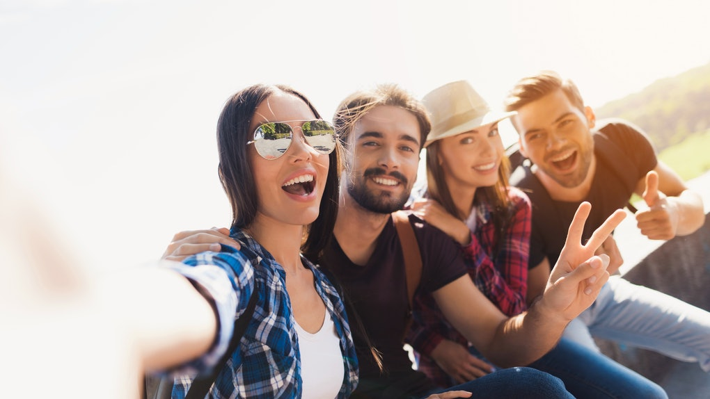 A group of backpackers smile and take a selfie on a sunny day.