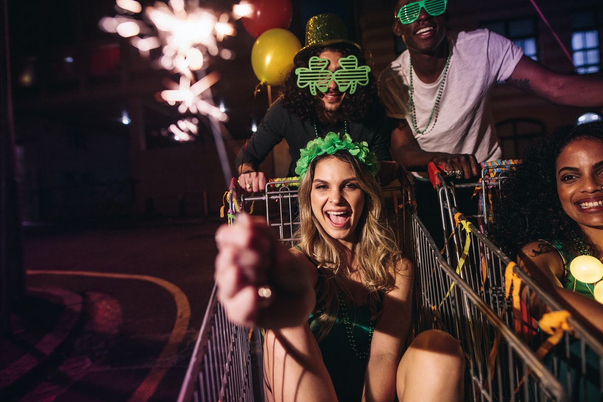 A group of friends celebrates St.Patrick's day with sparklers at night in the city.