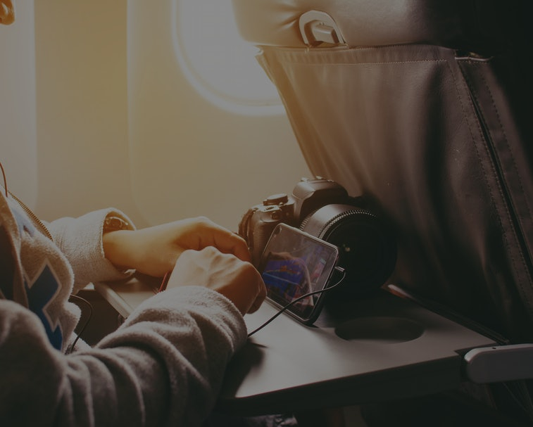 Man  watching video on mobile phone, while is sitting in plane near window with sun rays during his business trip. traveler guy is listening to music in headphones via cell telephone