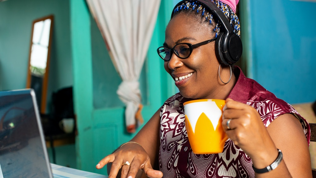 happy mature african woman is sitting at home working laptop, listening to music, and drinking coffee