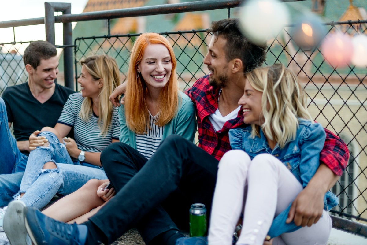 A group of friends laughs while hanging out and enjoying beers on a roof.