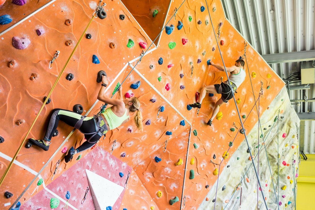 An athletic couple rock climbs on a colorful wall in a gym.
