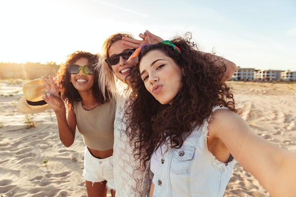 Three happy friends dressed in summery outfits smile for a selfie on a beach.