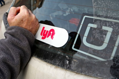 This is a Lyft logo being installed on a Lyft driver's car who also drives for Uber on in Pittsburgh