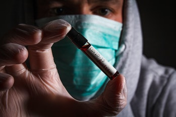 Doctor with respirator mask hold positive blood test of coronavirus