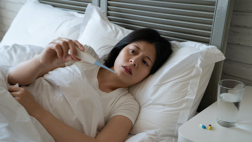 sick asian woman in bed taking temperature