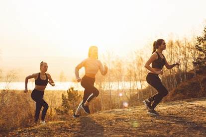 A group of girls jogging, climbing the mountain in the morning sun.