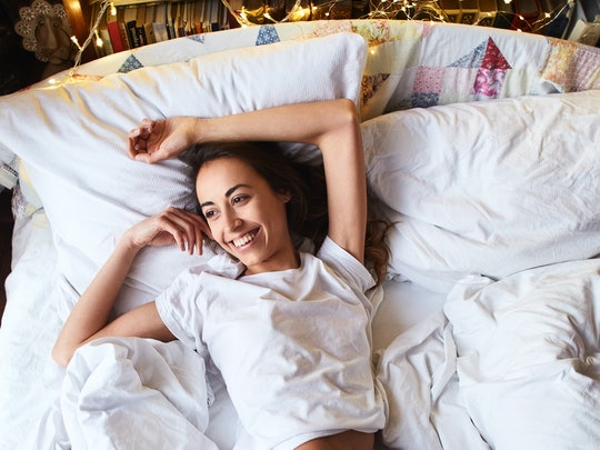 top view of a bright sexual smiling Girl in white t-shirt and shorts, lying on the bed with white bed sheets. Cozy winter mood in bedroom.