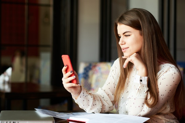 Attractive businesswoman is talking to her manager using FaceTime on her smartphone in the cafeteria. Successful female is discussing office problems on the weekend in the coffee shop.