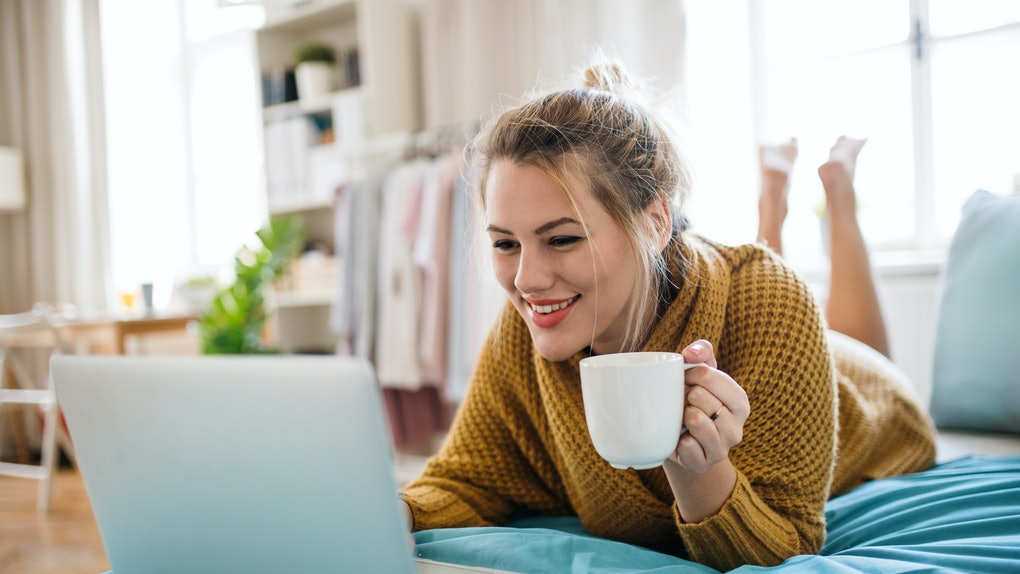 A woman in a yellow sweater holding a cup of coffee lays down in bed with her laptop.
