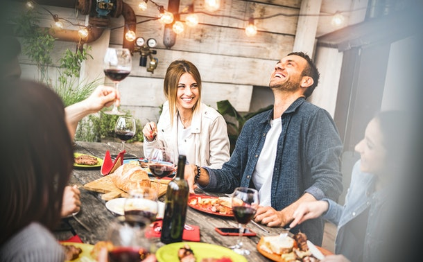 A group of friends enjoys tacos and red wine at an outdoor restaurant.