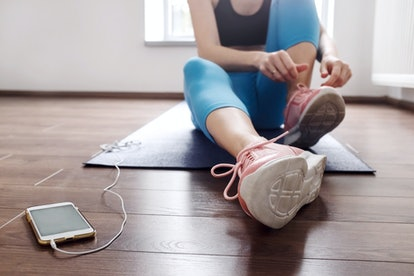 Fitness sport woman in fashion sportswear lacing sport footwear for running and smartphone fit application . Healthy lifestyle and sport concept.