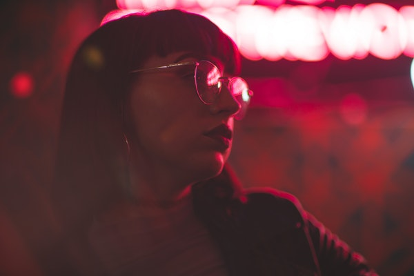 Girl with glasses in neon red lights