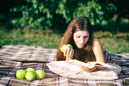 Cute young girl lying on a pillow, eating green apple and read a book in a park. A perfect picnic photo