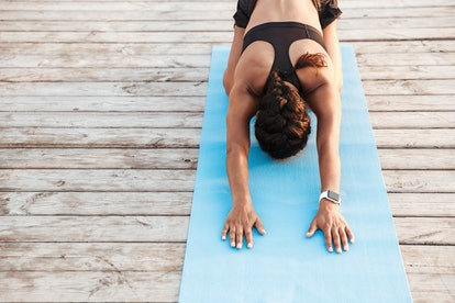 Photo of african american woman wearing sportive clothes stretching her body on finess mat while doing workout by seaside in morning