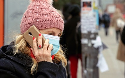 A woman wearing a surgical mask talks on the phone while waiting for a bus at a bus stop in Belgrade...