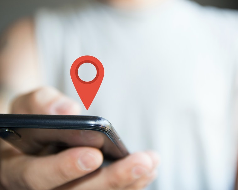 digital composite of person holding phone location icon