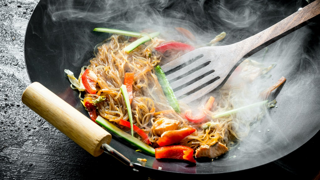 Hot wok Chinese cellophane noodles in a pan with a spatula. On black rustic background