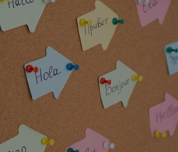 Learning Foreign Language concept. Handwritten Flashcards with Hello in other languages pinned on a cork board. Selective focus