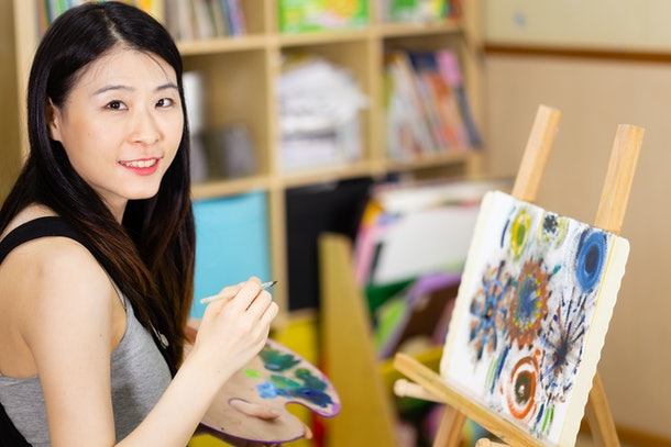 Asian American artist painting oil painting on an easel