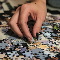 Young woman doing puzzle at home