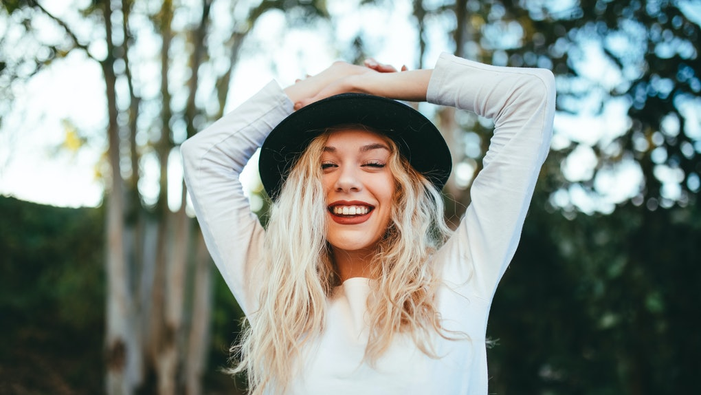 Happy girl in nature wearing a hat with black phone with green background white t-shirt