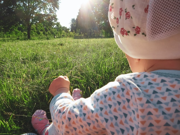 Baby girl looking at the dawn of the sun in the park