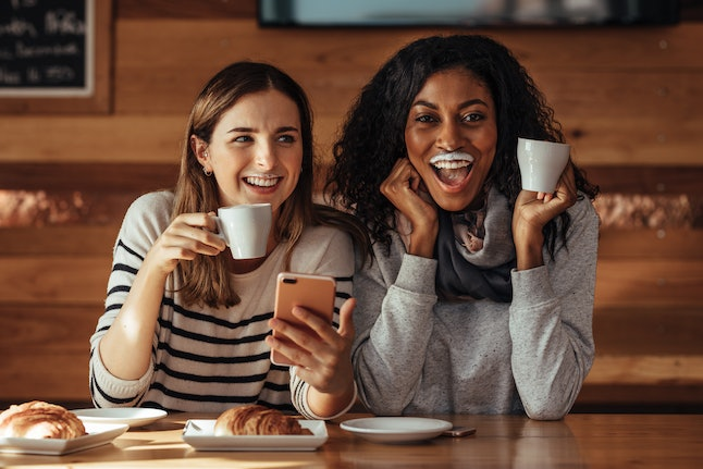 Two women drinking coffee and smiling with a milk mustache in coffee shop. Friends sitting at a cafe with coffee and snacks on the table holding a mobile phone.