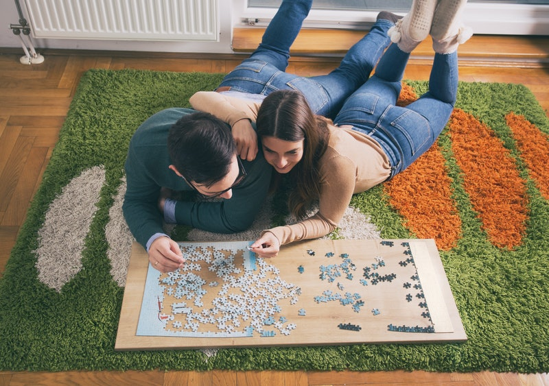 Top view of young couple laying on floor and doing puzzle