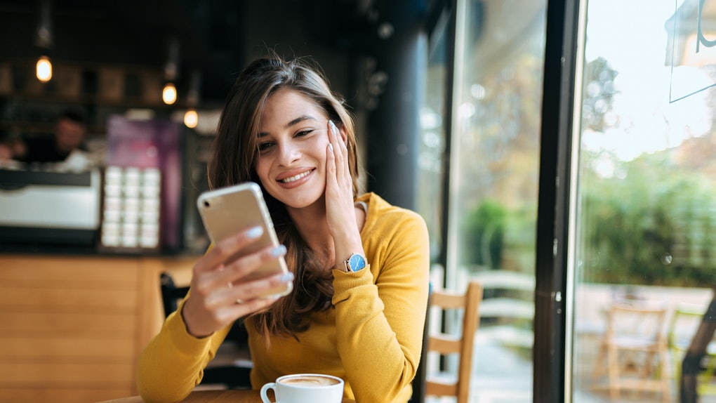 Young smiling woman using smarphone in the cafe. Front view.