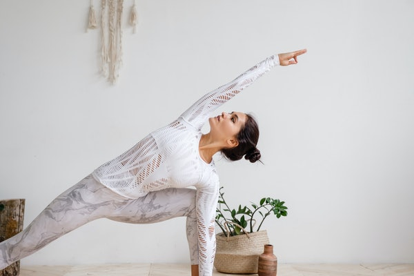A woman dressed in workout pants and a long-sleeve top strikes a yoga pose at home in a bright room.