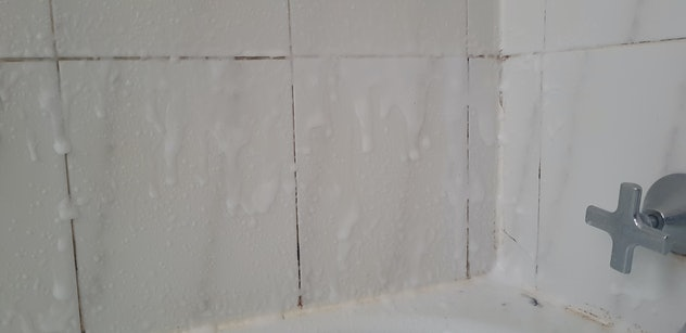 Mouldy Bathroom tiles covered with white foam spray cleaner