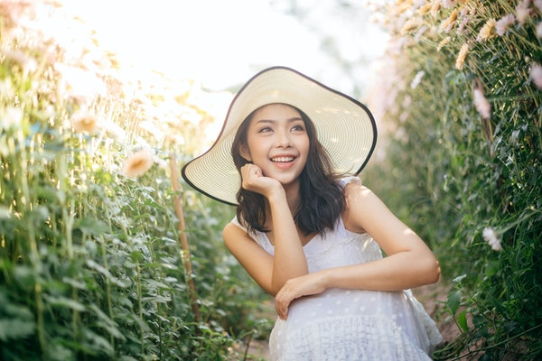 outdoor portrait of a beautiful asia woman. attractive cute girl in a field with flowers