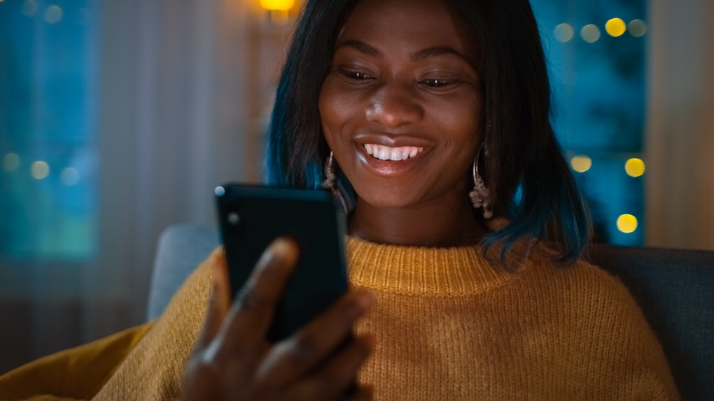 A woman in a yellow sweater holds up her iPhone and smiles.