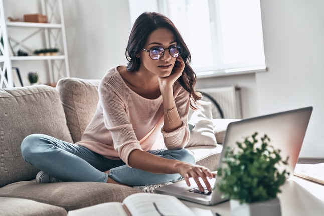 A woman wearing glasses, jeans, and a pink sweatshirt types on her computer while sitting on a gray couch in her living room.