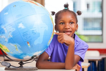 African girl at school with earth globe in background, geography and education concept.