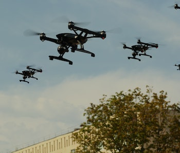 Swarm of Quadcopters Drones In The Air Over City. Army invasion