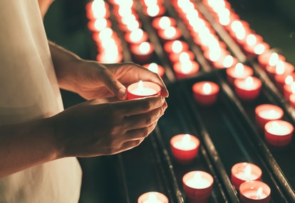 Woman holding candle near altar in church.