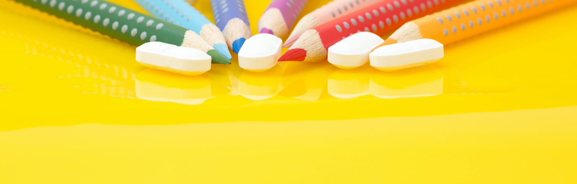 Medication for children concept. Color pencils and drugs on yellow background
