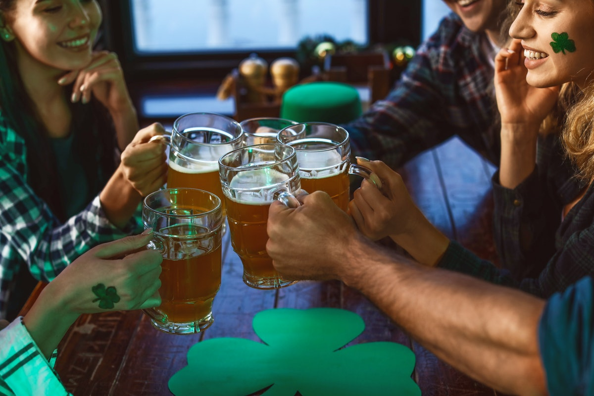 A group of friends dressed up in green for St. Patrick's Day toast their beers at a bar.