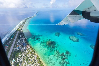 Tuvalu under the wing of the airplane. Aerial view of Funafuti atoll and airstrip of international a...
