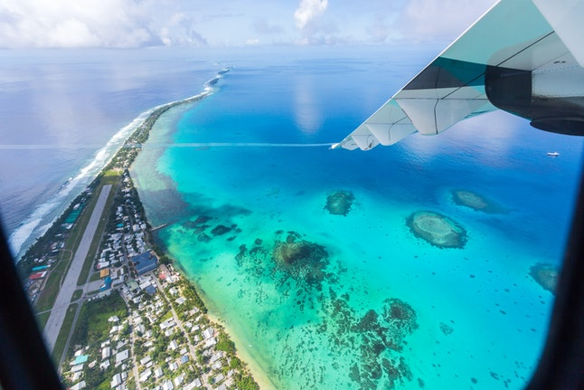 Tuvalu under the wing of the airplane. Aerial view of Funafuti atoll and airstrip of international airport in Vaiaku from air. Fongafale motu. Island nation in Polynesia, South Pacific Ocean, Oceania