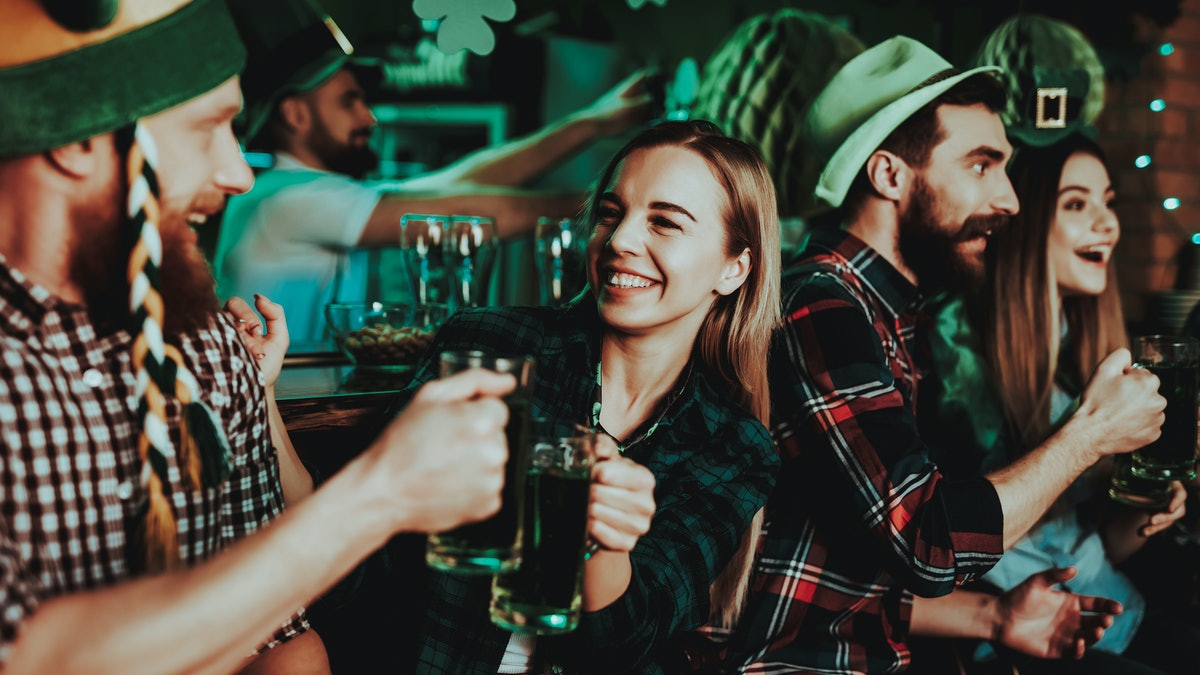 A group of friends hangs out in a bar on St. Patrick's Day, and wears flannels and green attire.