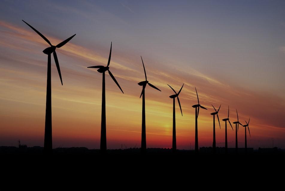 Wind turbines farm at beautiful orange sunset.