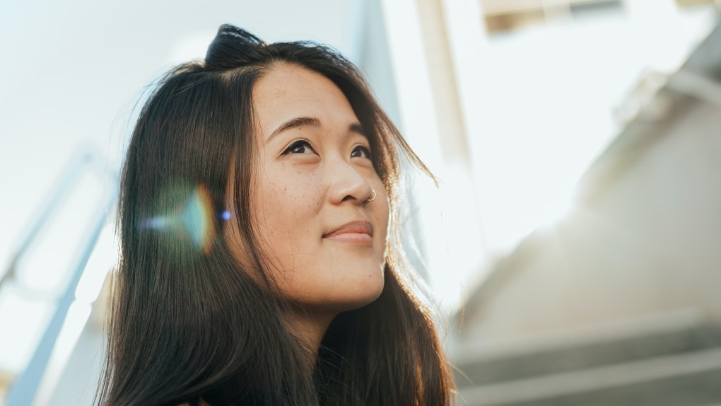 dreamy asian woman looking towards sky