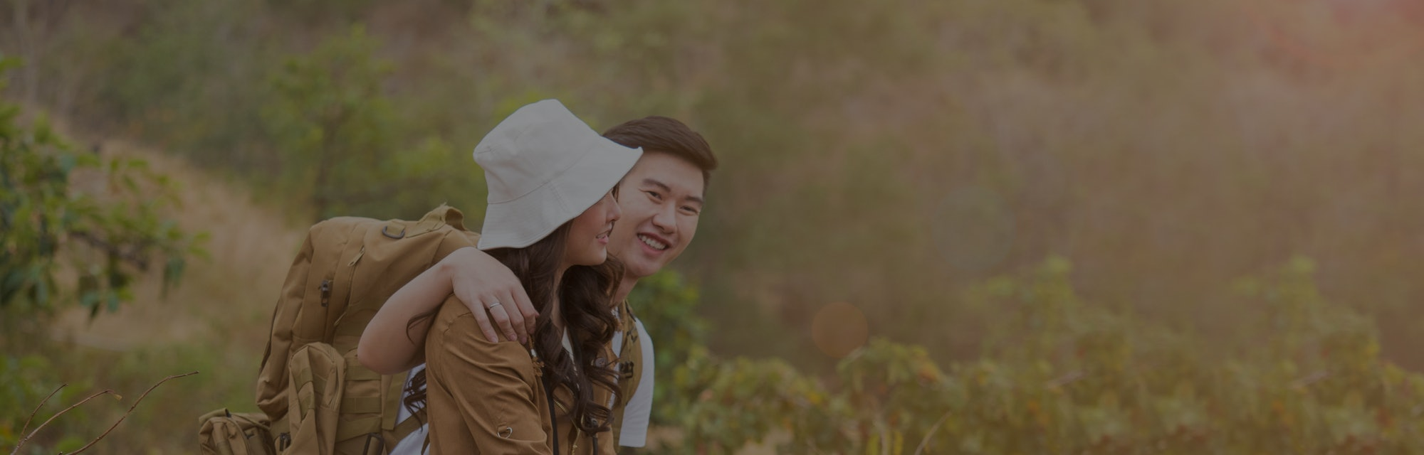 Young Asian couple, newly weds or lovers exploring forest, green naature. Tourist, backpack adventure enjoying the scenery of the natural park.
