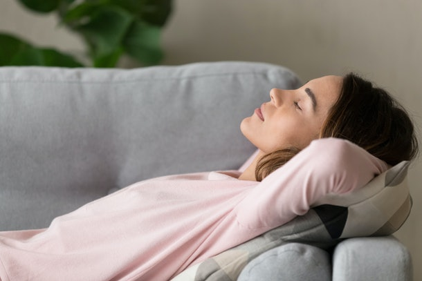 A woman wearing a pink sweater sleeps on a gray couch.