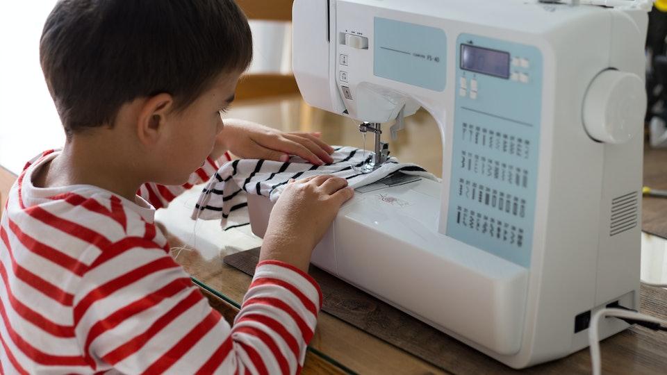 a boy sews on a sewing machine