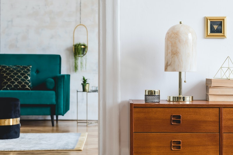 Stylish composition of open space interiors with wooden commode, velvet sofa, marble table lamp, books, black pouf, plants, gold photo frame and elegant accessories. Modern design interior. Template.