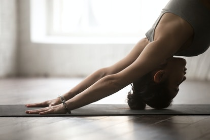 Young attractive woman practicing yoga, standing in Downward facing dog exercise, adho mukha svanasa...